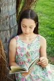 Libro de lectura adolescente lindo de la muchacha que se sienta en hierba verde Imagen de archivo