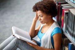 Libro de lectura africano de la muchacha del estudiante en la biblioteca Imagen de archivo