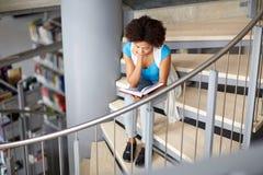 Libro de lectura africano de la muchacha del estudiante en la biblioteca Fotos de archivo