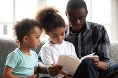 Libro de lectura afroamericano del papá a los pequeños niños fotografía de archivo libre de regalías