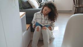 Libro de lectura afroamericano hermoso de la mujer en casa imagen de archivo libre de regalías