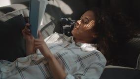 Libro de lectura afroamericano hermoso de la mujer en casa metrajes