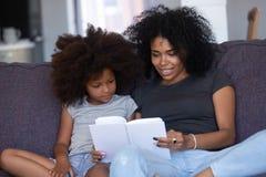 Libro de lectura afroamericano de la mamá a poca hija en casa foto de archivo libre de regalías