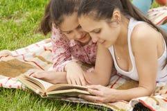 Libro de lectura al aire libre sonriente de las muchachas Imagen de archivo