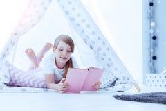 Libro de lectura alegre de la muchacha mientras que miente en piso Fotografía de archivo libre de regalías