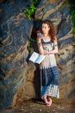 Libro de lectura americano joven de la mujer, mandando un SMS en el teléfono celular, viaje Fotos de archivo libres de regalías