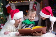 Libro de lectura amistoso de la familia el la tarde de la Navidad Fotos de archivo libres de regalías
