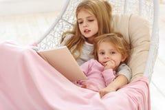 Libro de lectura amistoso de la familia junto Imágenes de archivo libres de regalías