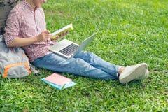 Libro de lectura asiático del estudiante mientras que se sienta en la hierba verde Imágenes de archivo libres de regalías