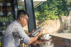 Libro de lectura asiático del hombre por la mañana imagen de archivo libre de regalías