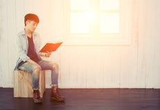 Libro de lectura asiático hermoso del hombre que se sienta en la silla de madera cerca Imagenes de archivo
