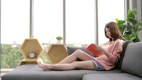 Libro de lectura asiático joven de la mujer el día de fiesta Un primer del libro abierto de mentira de la muchacha feliz joven en metrajes