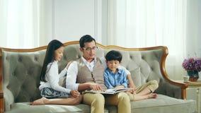 Libro de lectura asiático de la hija y del hijo del padre junto en casa metrajes