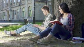 Libro de lectura asiático de la muchacha debajo del árbol y mirada del individuo que usa el ordenador portátil, timidez almacen de metraje de vídeo