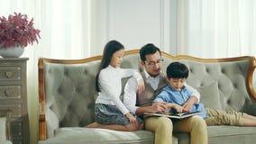 Libro de lectura asi?tico del padre con la hija y el hijo almacen de metraje de vídeo