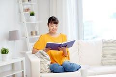 Libro de lectura asiático joven sonriente de la mujer en casa Imágenes de archivo libres de regalías