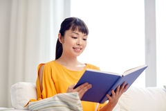 Libro de lectura asiático joven sonriente de la mujer en casa Imagen de archivo libre de regalías