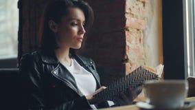Libro de lectura atractivo de la estudiante en sentarse de relajación del café en la tabla solamente metrajes