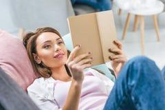 libro de lectura atractivo de la muchacha mientras que miente en el sofá Fotos de archivo