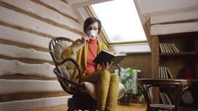 Libro de lectura atractivo de la mujer adulta mientras que bebe el café en ático metrajes