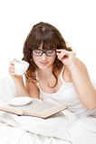 Libro de lectura bonito de la muchacha y café de consumición Fotos de archivo