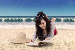 Libro de lectura bonito de la mujer en la playa Fotos de archivo libres de regalías