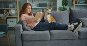 Libro de lectura bonito de la mujer joven y perro de caricia que se sientan en el sofá en casa metrajes