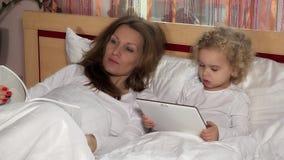Libro de lectura cansado de la madre y su película de observación de la muchacha dulce de la hija en la tableta almacen de metraje de vídeo