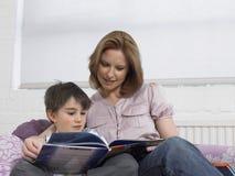 Libro de lectura cariñoso de la madre y del hijo en cama Imagen de archivo