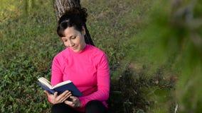 Libro de lectura caucásico de la mujer en el parque metrajes