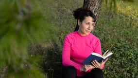 Libro de lectura caucásico joven de la mujer en el parque metrajes