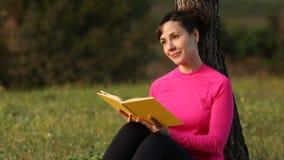 Libro de lectura caucásico joven de la mujer en el parque verde metrajes