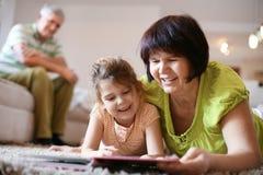 Libro de lectura caucásico de la abuela a la nieta fotografía de archivo