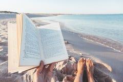 Libro de lectura cerca del mar fotos de archivo
