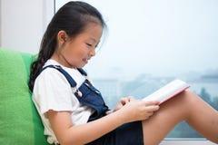 Libro de lectura chino asiático de la niña en el alféizar imágenes de archivo libres de regalías