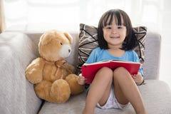 Libro de lectura chino asiático sonriente de la niña con el oso de peluche Imagenes de archivo