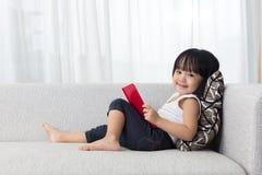 Libro de lectura chino asiático sonriente de la niña en el sofá Imágenes de archivo libres de regalías