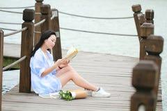 Libro de lectura chino de la muchacha La mujer joven hermosa rubia con el libro se sienta en el puente cerca de la cerca Imagen de archivo