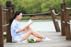 Libro de lectura chino de la muchacha La mujer joven hermosa rubia con el libro se sienta en el puente cerca de la cerca Fotografía de archivo
