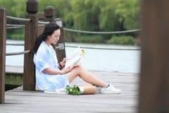 Libro de lectura chino de la muchacha La mujer joven hermosa rubia con el libro se sienta en el puente cerca de la cerca Imagen de archivo libre de regalías