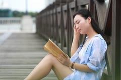 Libro de lectura chino de la muchacha La mujer joven hermosa rubia con el libro se sienta en la tierra Fotografía de archivo libre de regalías