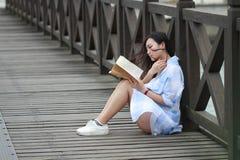 Libro de lectura chino de la muchacha La mujer joven hermosa rubia con el libro se sienta en la tierra Imagen de archivo libre de regalías