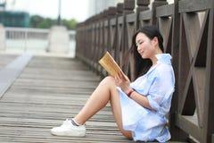 Libro de lectura chino de la muchacha La mujer joven hermosa rubia con el libro se sienta en la tierra Imagen de archivo