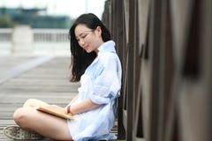 Libro de lectura chino de la muchacha La mujer joven hermosa rubia con el libro se sienta en la tierra Fotos de archivo libres de regalías