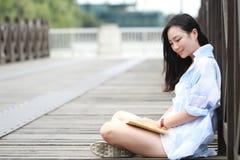Libro de lectura chino de la muchacha La mujer joven hermosa rubia con el libro se sienta en la tierra Imágenes de archivo libres de regalías