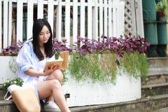 Libro de lectura chino de la muchacha La mujer joven hermosa rubia con el libro se sienta en los pasos Imagen de archivo libre de regalías