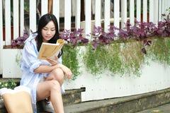 Libro de lectura chino de la muchacha La mujer joven hermosa rubia con el libro se sienta en los pasos Fotografía de archivo