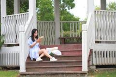 Libro de lectura chino de la muchacha La mujer joven hermosa rubia con el libro se sienta en los pasos del pabellón Foto de archivo