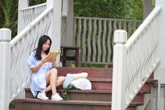Libro de lectura chino de la muchacha La mujer joven hermosa rubia con el libro se sienta en los pasos del pabellón Imagenes de archivo