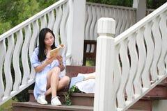 Libro de lectura chino de la muchacha La mujer joven hermosa rubia con el libro se sienta en los pasos del pabellón Imágenes de archivo libres de regalías
